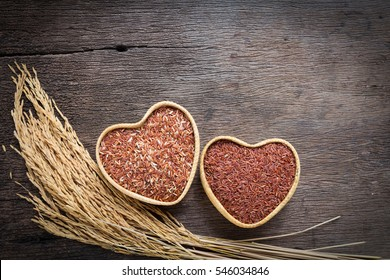 Organic rice grain,brown rice in heart shape over wooden background
