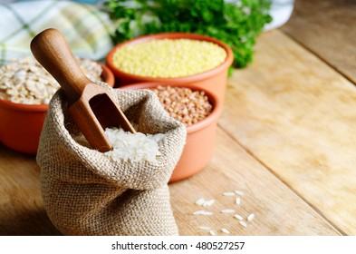 Organic rice grains in burlap sack on kitchen table
