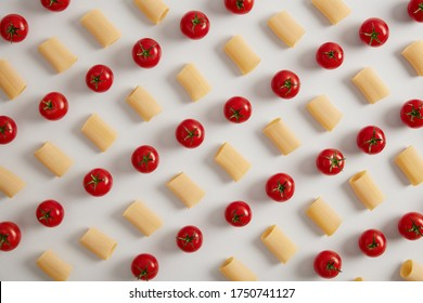 Organic rigatoni pasta and red cherry tomatoes arranged in rows on white studio background. Creative layout for menu. Food concept. Healthy dry macaroni pasta. Above shot, view from overhead