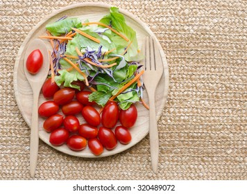 Organic Salad on wooden plate and natural floor