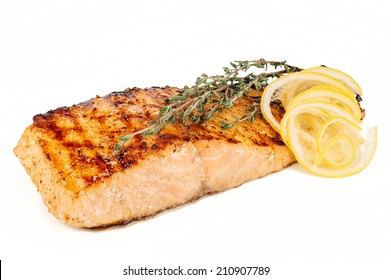 Organic salmon red fish fillet grilled with spices, lemon slices and rosemary on white background, traditional seafood dish
