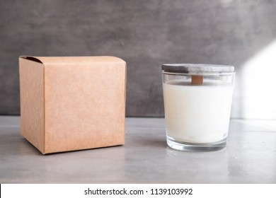 Organic scented soy candle with craft box on grey concrete cement table. Loft interior decor, minimalism concept.  Closeup, copy space for text