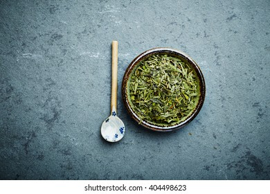 Organic Sencha green tea with ceramic spoon on a stone background