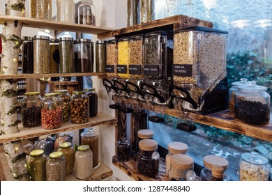 Organic shop interior. Display of glass jars on shelves filled with fresh and dry produce in grocery store.