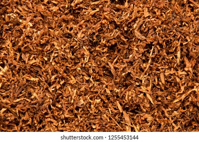 Organic shredded tobacco leaves fills entire frame from above, smoked in pipes and rolled into cigarettes. Native american medicine.