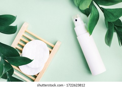 Organic skin care and beauty treatment blue background. Cosmetic product white spray bottle container, facial cleanser cotton pads, fresh plant leaves, top view pastel toned.