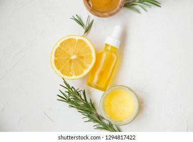 Organic skincare ingredients with lemon and rosemary oil bottle and herb, manuka honey and balm salve, top view on white background