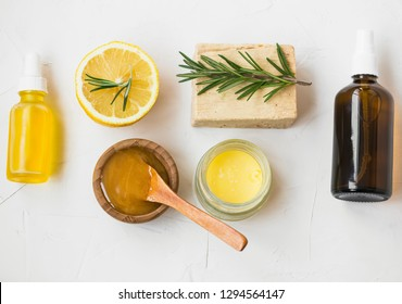 Organic skincare ingredients with manuka honey, lemon, rosemary, face oil, salve balm , natural soap and face water spray, natural herbal spa cosmetic products top view