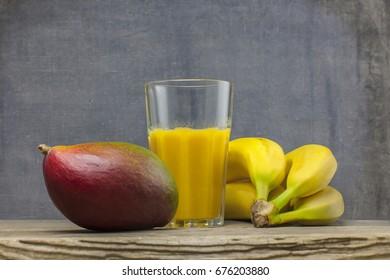 organic smoothie mango and bananas juice glass on wooden background