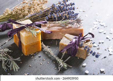 organic soaps with blue and white lavender bouquets on dark wooden table
