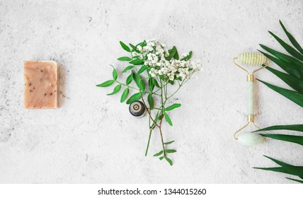 Organic spa. natural herbal skincare ingredients with herbs and plants, natural soap, essential oil, jade face roller, wellness and home spa products, top view