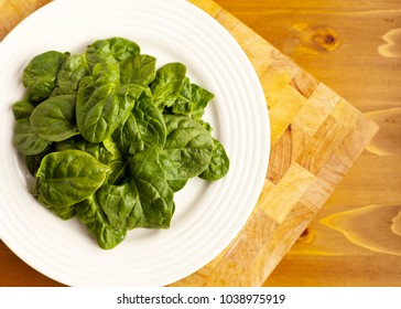 Organic Spinach on White Plate and placed on Wooden Chopping Board