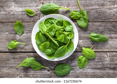 Organic spinach, plate with leaves, green vegetables, fresh food and healthy diet concept