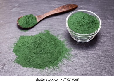 Organic spirulina algae powder on black slate platter background, closeup