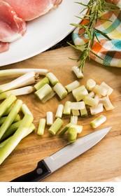 organic spring onion and raw bacon on a wooden board to prepare irish colcannon