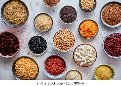Organic superfood assortment in bowls. With raw peas, beans, wild rice, lentil, Goji berries, cranberry, couscous, linseeds on white rusty background. Above view.