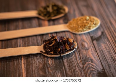 Organic tea herbs on wooden sppons including mint and dandelion dry grains and seeds ready to be made for hot or cold infusions selective focus herbalism