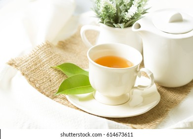 organic tea in white cup with green leaf , Tea ceremony time concept