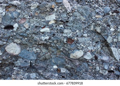Organic texture: limestone, marble or granite gray rock consists of a gray base and includes a variety of stones of various sizes and shapes of white and brown