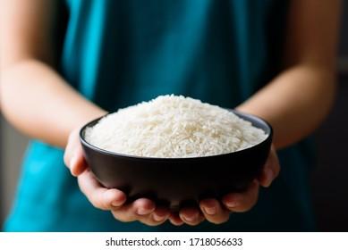 Organic Thai Jasmine rice grain in a bowl holding by hand