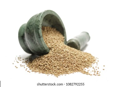 Organic Thyme Seeds (Trachyspermum ammi) or ajowan on marble pestle and over white background.