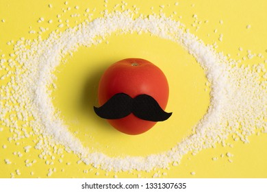 Organic tomato with a mustache standing in a circle of salt on a bright yellow pastel background