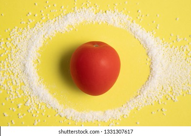 Organic tomato standing in a circle of salt on a bright yellow pastel background