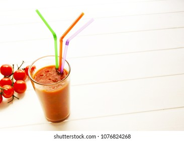Organic tomatoes and glass with straws on white surface