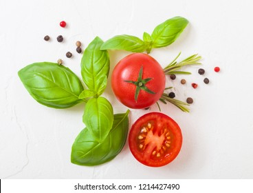 Organic Tomatoes on the Vine with basil and pepper on white kitchen stone background