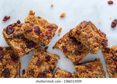 Organic vegan flapjack made with dates, cranberries and apricots with no animal products for super healthy diet on a white marble base