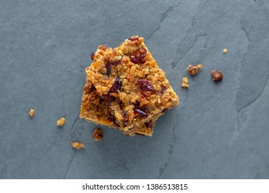 Organic vegan flapjack made with dates, cranberries and apricots with no animal products for super healthy diet on a grey slate base