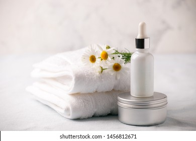 Organic vegan natural cosmetics concept. Chamomile flowers and cosmetic bottles of cream and serum essential on white background. Zero waste cosmetic package