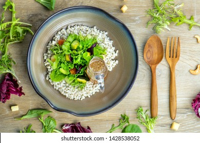 Organic vegetable Barley salad fresh, clean, healthy food With fresh lettuce citrus fruit, crab sesame on the plate eat with vinaigrette dressing .food menu Top view, white wood table background