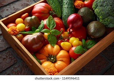 Organic Vegetable box with large, cherry tomatoes, basil, cucumbers, red onions, broccoli and avocado.