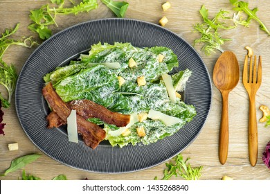 Organic vegetable Caesar salad fresh, clean, healthy food With fresh lettuce crispy bacon, crab sesame on the plate eat with vinaigrette dressing .food menu Top view, white wood table background