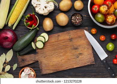 Organic vegetables assortment on kitchen table with cutting board and knife, vegetarian recipe, top view, copy space