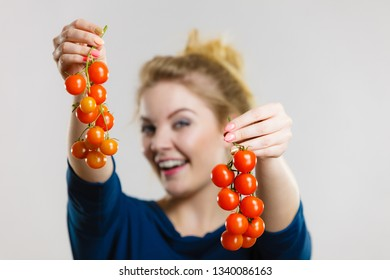 Organic vegetables and food concept. Happy positive smiling woman holding fresh cherry tomatoes