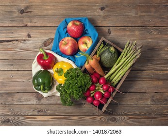 Organic vegetables and fruits in reusable cotton bags on wooden background, eco-friendly lifestyle and shopping, zero waste, plasticfree packing