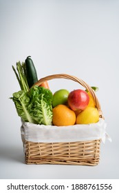 Organic vegetables and fruits in wicker basket isolated on white background.