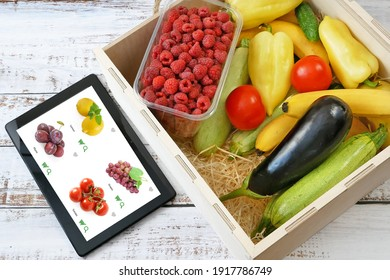 Organic Vegetables and fruits in wooden box and tablet pc, online market, green grocery delivery at home concept