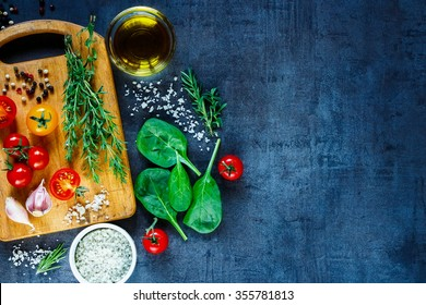 Organic vegetarian ingredients, olive oil and seasoning on rustic wooden cutting board over dark vintage background with space for text, top view. Healthy food, vegan or diet nutrition concept.