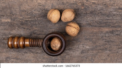 Organic walnuts with nut cracker on a wooden table, wooden background. Crushing, healthy.