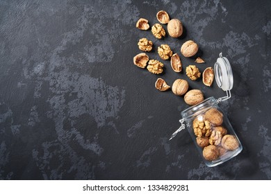 Organic walnuts in an open glass jar on black stone background, with copy space. Top view.
