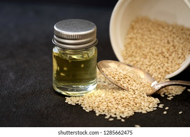 organic  white sesame seeds in wooden spoon with oil bottle