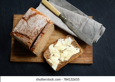 Organic whole grain bread with fresh homemade butter over dark stone rustic background and wooden desk. Top view.