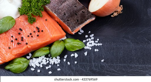Organic wild king salmon fillet with fresh herbs, spices and vegetables on black stone board. Healthy cooking concept.
