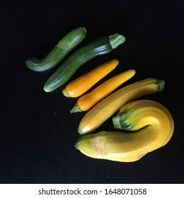 ORGANIC YELLOW AND GREEN MISSHAPEN COURGETTES ON BLACK