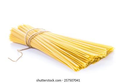 Organic yellow spaghetti pasta on a white background.