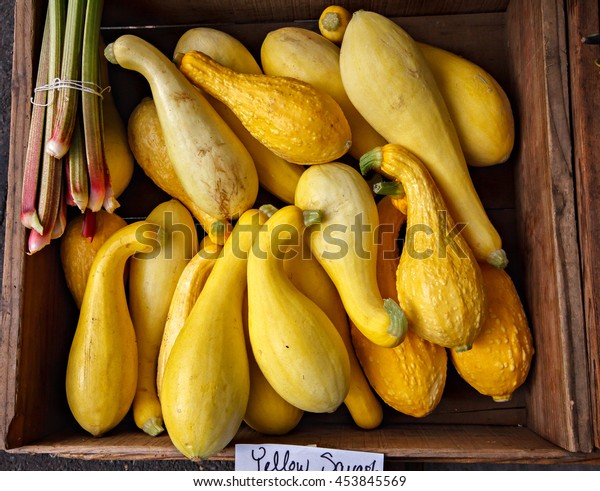 Organic yellow squash in a wooden box at a local farmers market.