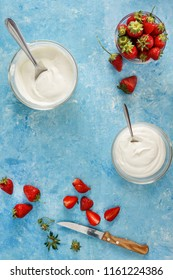 Organic yogurt in a bowl with freshly cut strawberries on a blue concrete background. Top view and close-up. Flatlay.